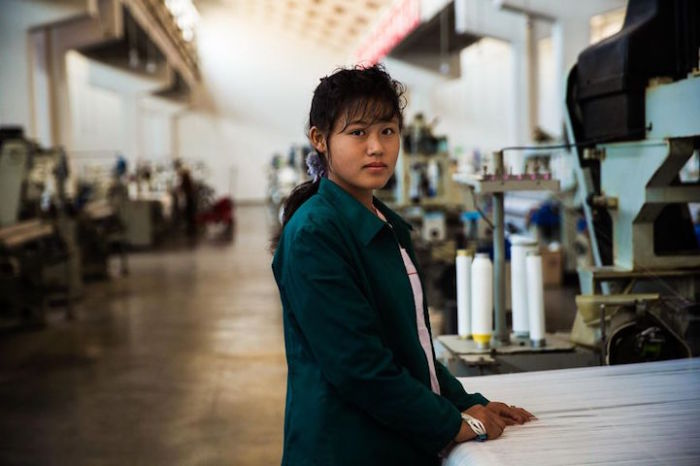 Девушка за работой на текстильной фабрике в Пхеньяне.