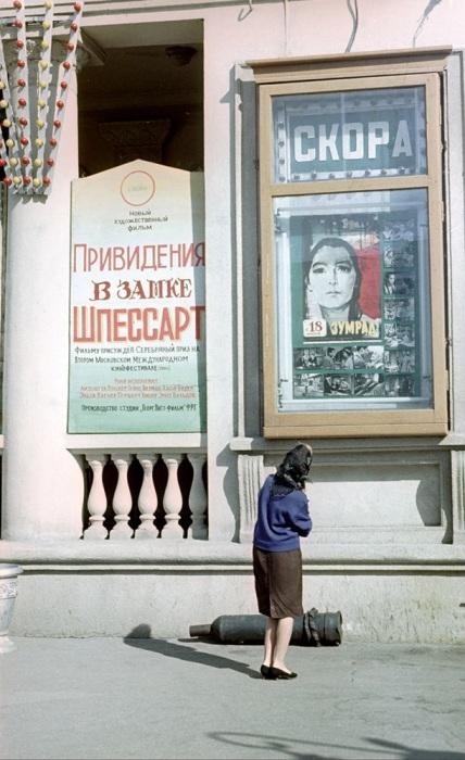 Женщина изучает афиши на здании кинотеатра «Победа».