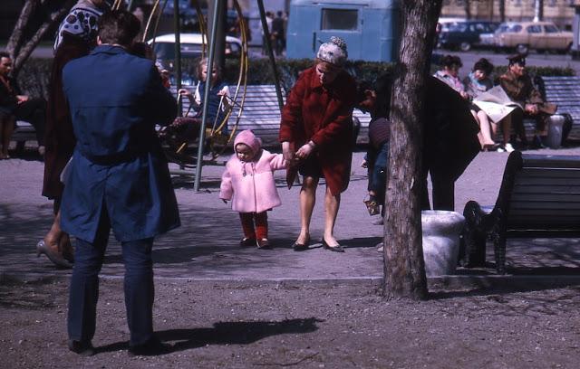 На детской площадке гуляют и взрослые, и дети.