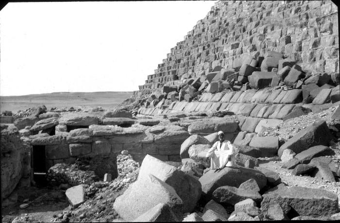 Человек сидит на камне перед пирамидой.