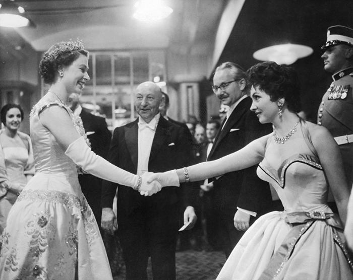 Джина Лоллобриджида пожимает руку королеве Елизавете II на премьере фильма «Поймать вора». Англия, Лондон, 1954 год.