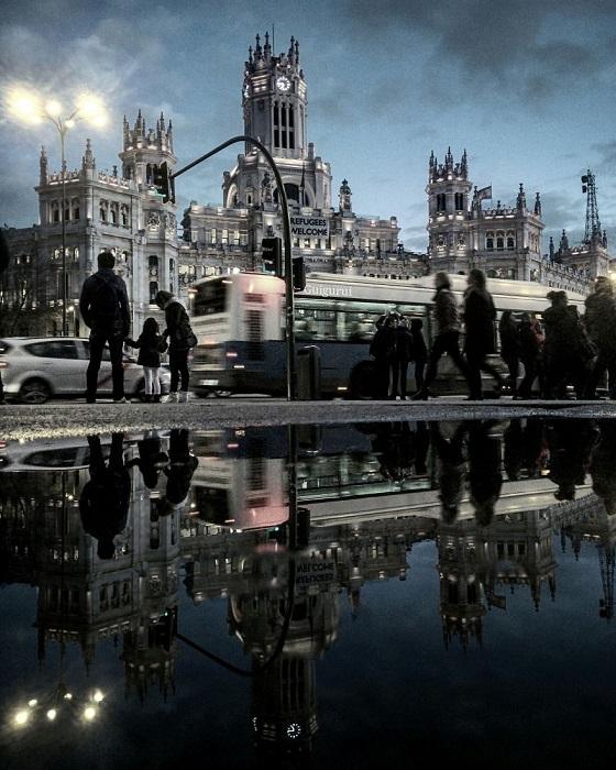 Спешащие по своим многочисленным делам жители вечернего города, отражающиеся в осенней луже.