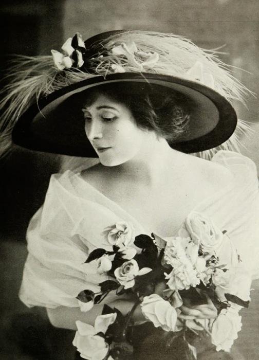 Красоту девушки украшает изысканная шляпа украшенная перьями и нежный букет белых роз.
