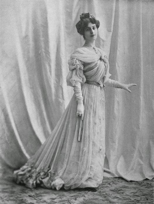 Девушка в платье украшенным драпировками на лифе и юбке.