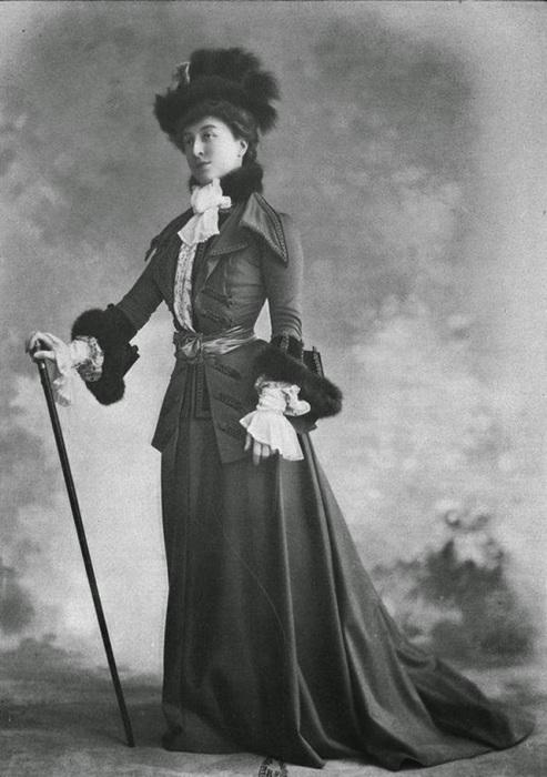 Костюм девушки дополнен великолепной меховой шляпой и элегантной тростью.