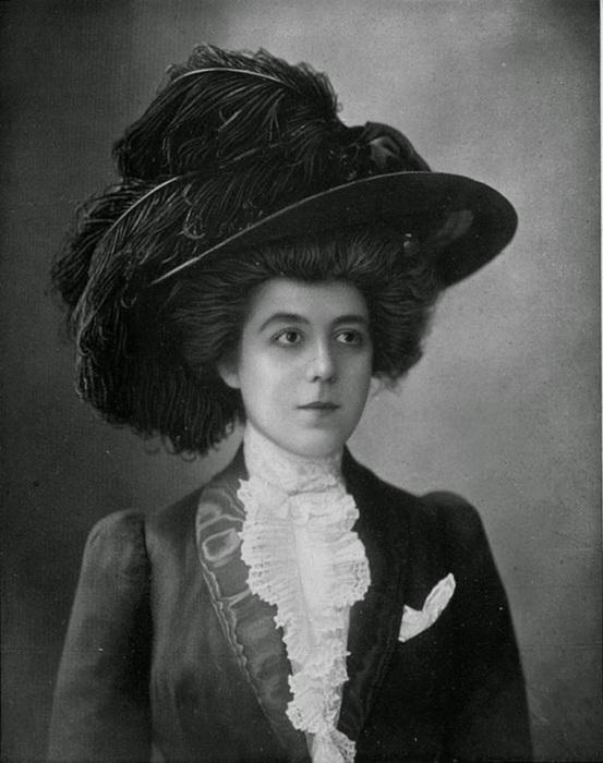 Пикантность костюму придает великолепная огромная шляпа украшенная перьями и пышная прическа девушки.
