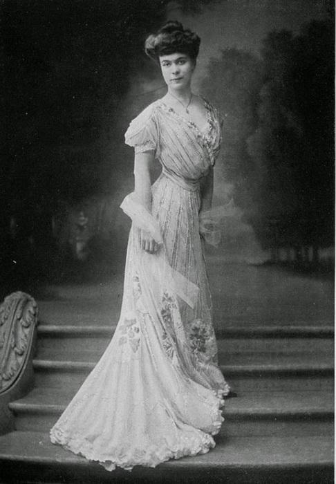 Девушка в платье из дорогого шелка, украшенного аппликацией из белого бисера.