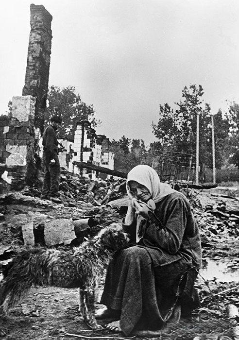 Женщина сидит на пепелище родного дома, разрушенного немцами.