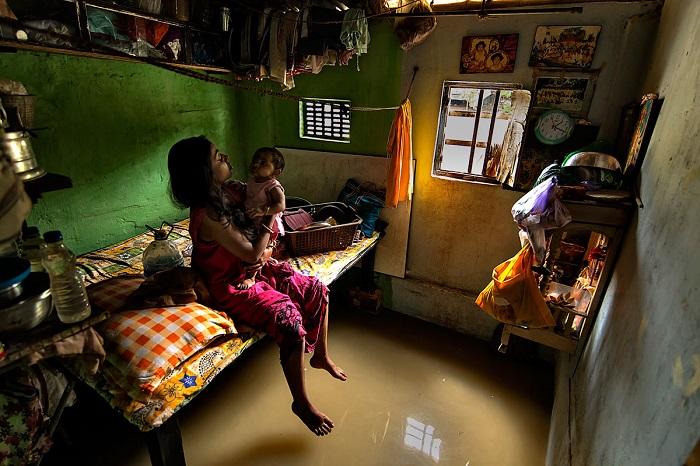 Мать играет с ребенком в затопленном помещении, вблизи берегов реки Ганг. (Калькутта, Западная Бенгалия, Индия, август 2013 года, Nikon D600).