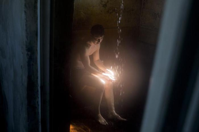 Житель села Акбасты моется под струей воды в своей ванной. Сельчане используют воду, которая еще осталась в Аральском море.