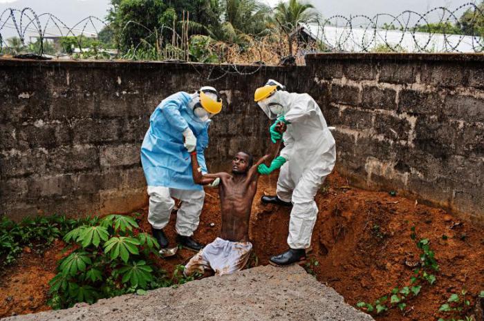 Медицинские сотрудники Центра лечения вируса Эбола Хастингс, которые возвращают пациента с вирусом назад в изолятор, из которого он пытался сбежать во время приступа лихорадки.