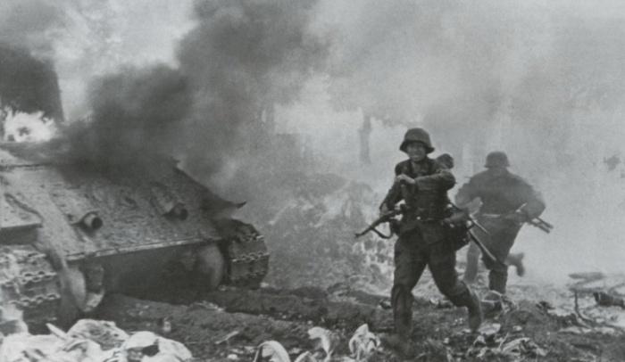Гренадёры меняют позицию в бою под Варшавой, пробегая мимо горящего советского танка Т-34.