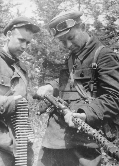 Два советских партизана осматривают трофейный немецкий пулемет MG-34.