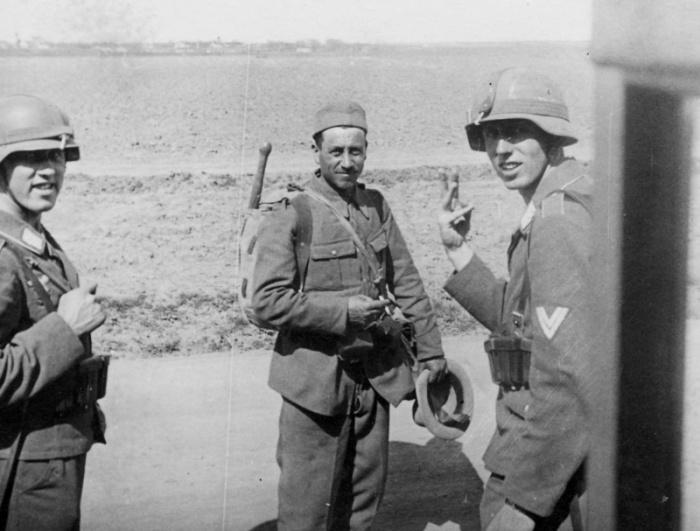Два солдата немецкой дивизии «Германн Геринг» общаются с румынским солдатом.
