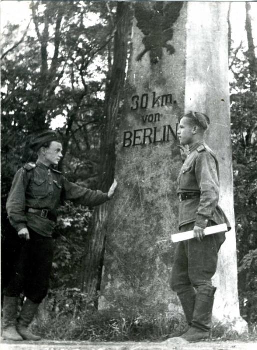 Двое советских военнослужащих у указателя.