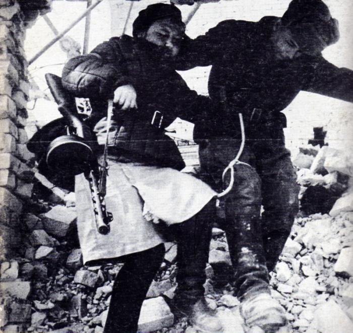 Девушка-санинструктор сопровождает раненого солдата в Сталинграде.