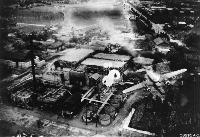Горящий самолёт 345-й бомбардировочной группы, сбитый зенитной артиллерией при бомбардировке японского нефтеперерабатывающего завода.
