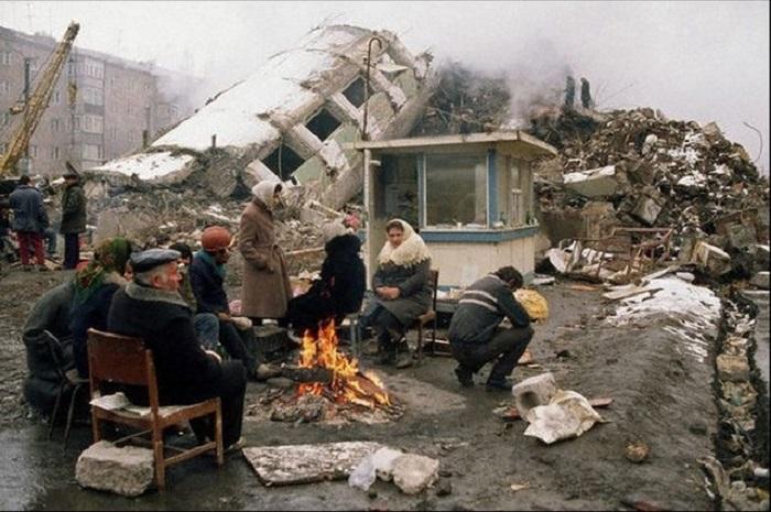 Люди, пережившие сильнейшее землетрясение на северо-западе Армении, пытаются согреться у костра.
