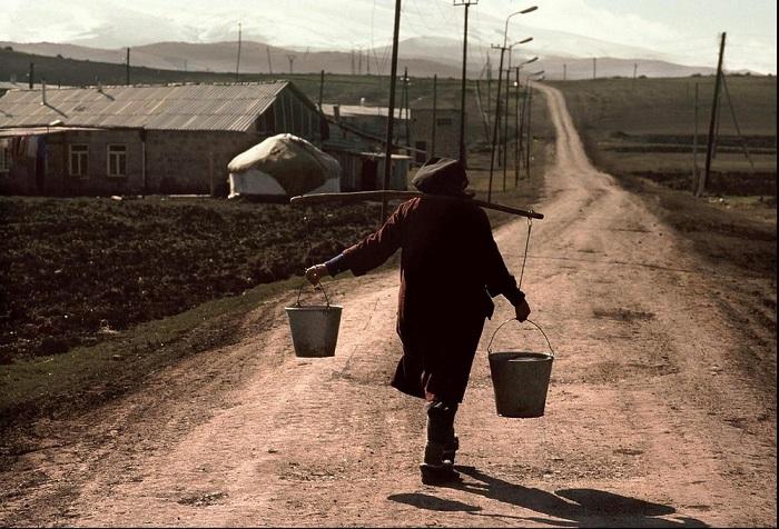Женщина с ведрами, наполненными питьевой водой, на дороге одного из сел Армении.