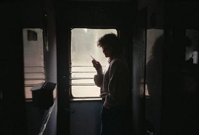 Девушка, курящая на закрытой площадке пассажирского железнодорожного вагона.