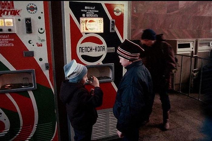 Мальчики покупают заграничную газировку «Пепси-кола», которая было очень популярна у детей, в торговом автомате в Москве.