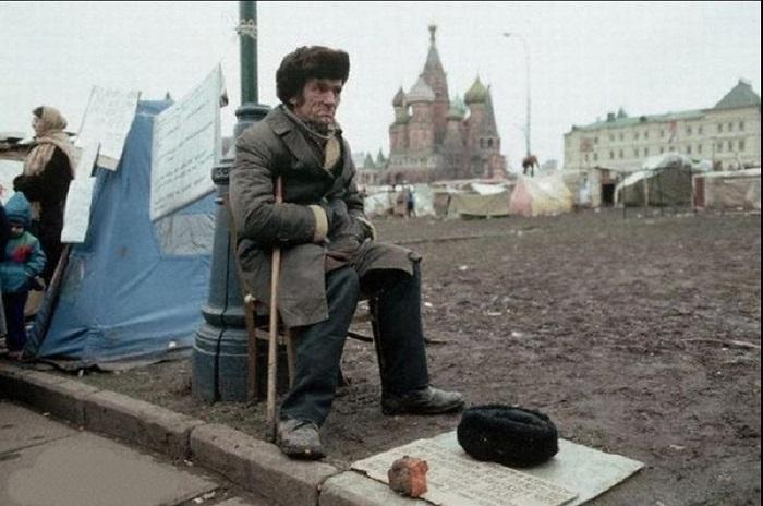 Советский бездомный, просящий милостыню у палаточного городка в Москве.