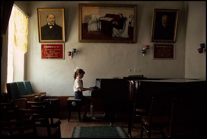 Пионерка музицирует под строгими и одобрительными взглядами великих композиторов (Узбекистан).