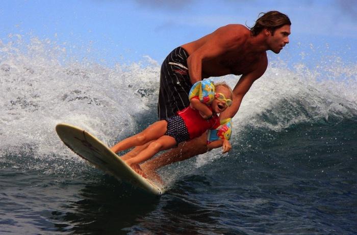 Папа обучает дочку сёрфингу.