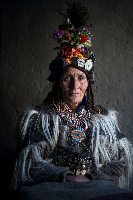 Пожилая женщина группы дрокпа, одета в платье с бусами, монетами и цветами.