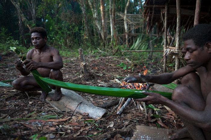 Мужчины подготавливают еду для запекания на костре.