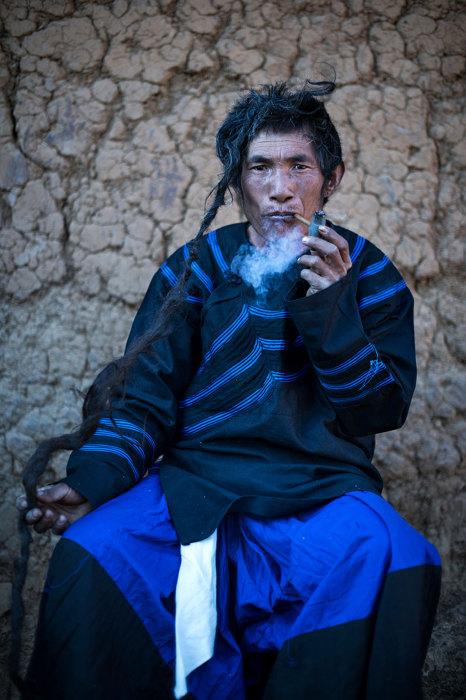 Представитель племени лоло курит трубку.