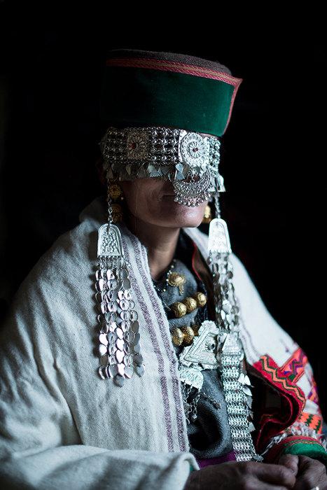 Шапка с украшениями, закрывающая лицо женщины.