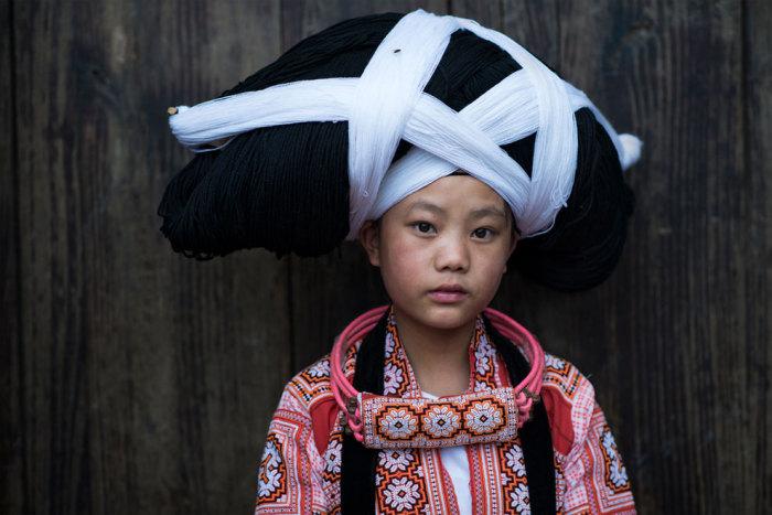 Девочка в торжественном шиньоне, который закреплен на деревянных рогах.