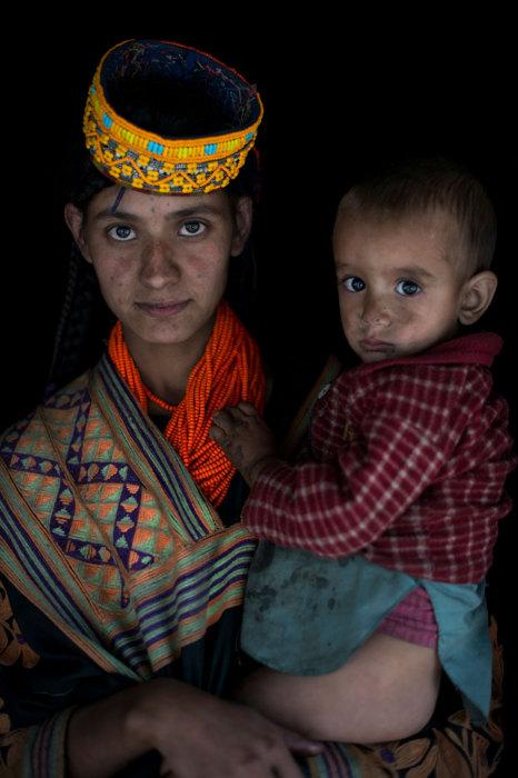 Женщина с ребенком на руках в многочисленных бусах и шапочке, украшенной бисером.