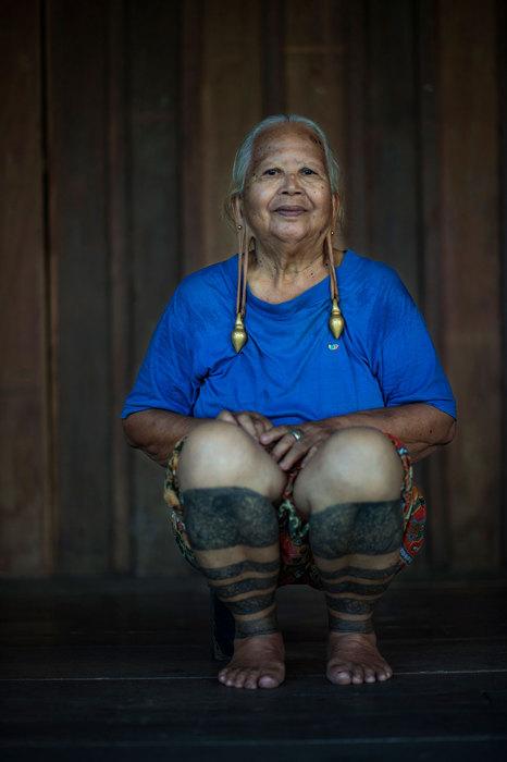 Пожилая женщина с татуировками на ногах.