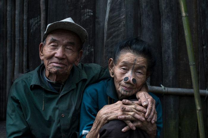 Супружеская пара сидит в обнимку возле своей хижины.
