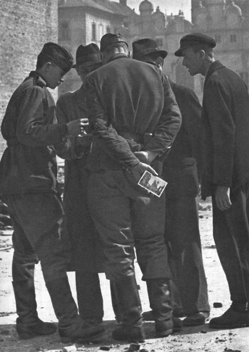 Житель Праги дарит советским солдатам открытки с видами города.