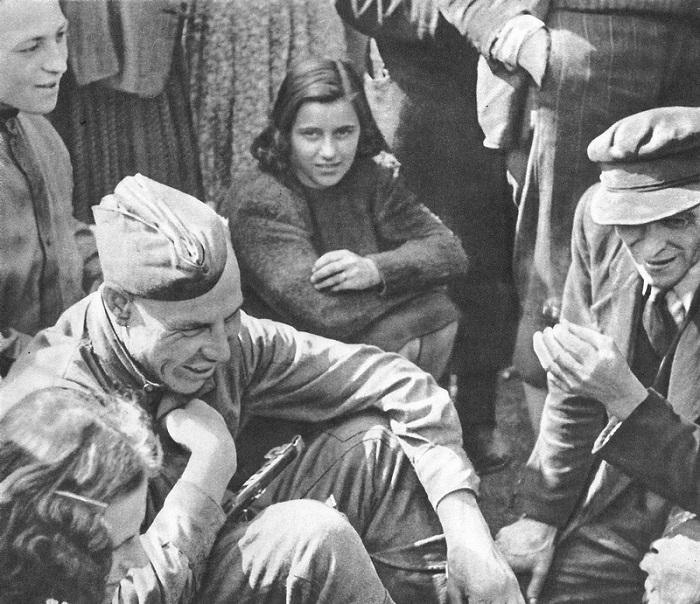 Советский солдат что-то рассказывает собравшимся вокруг него жителям Праги.