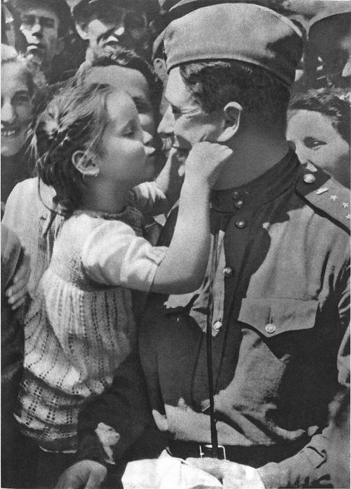 Чешская девочка играет с советским офицером, капитаном танковых войск.