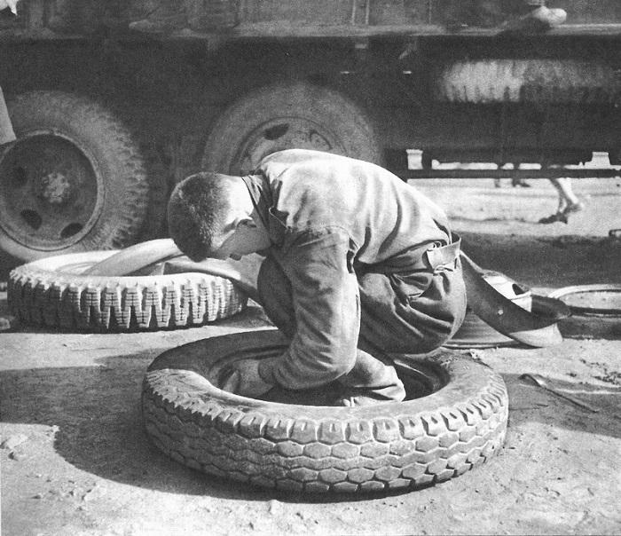 Советский солдат меняет камеру в автомобильном колесе.