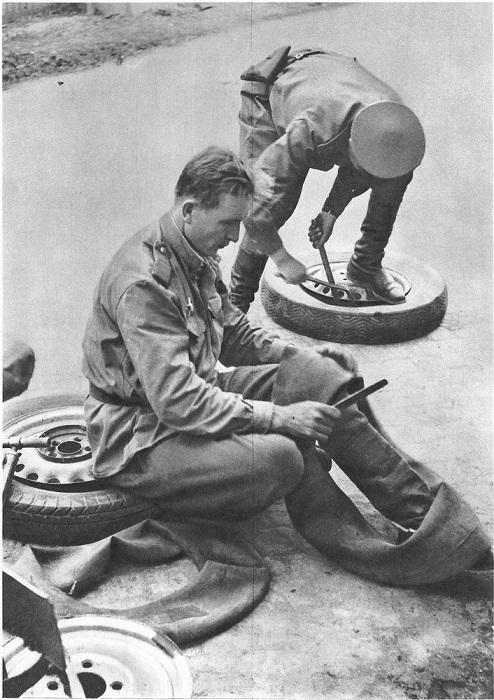 Советские солдаты ремонтируют автомобильные колеса.
