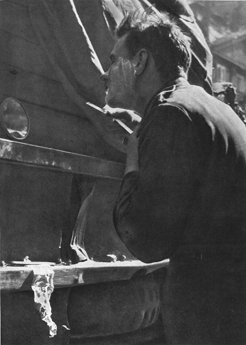 Солдат бреется в походных условиях — зеркало установлено в нишу кузова грузовика.