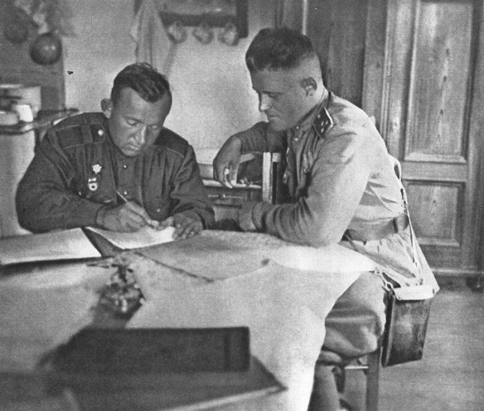 Советские старший сержант и старший лейтенант за столом в чешском доме.