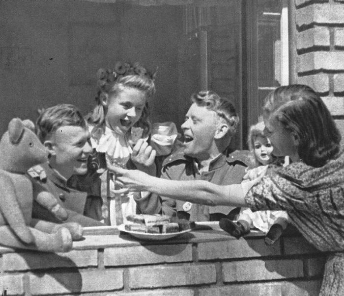 Чешские девочки угощают советских офицеров пирожными.