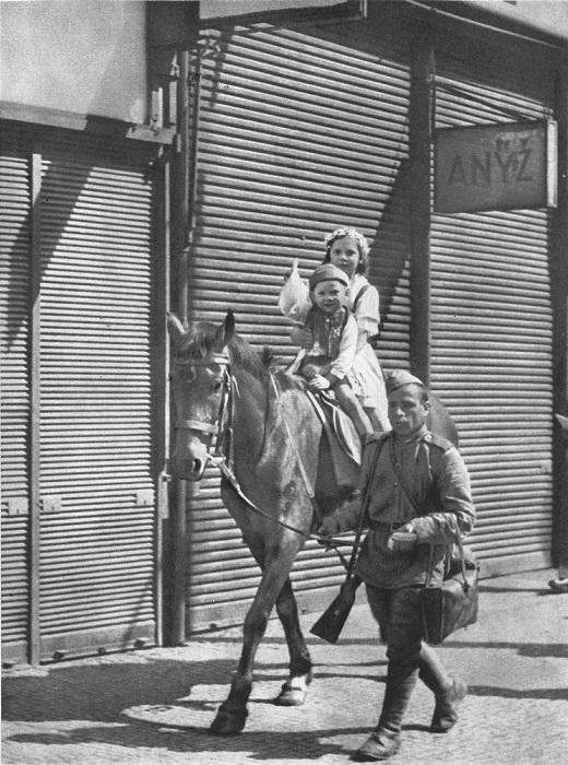 Советский солдат катает чешских детей на лошади.