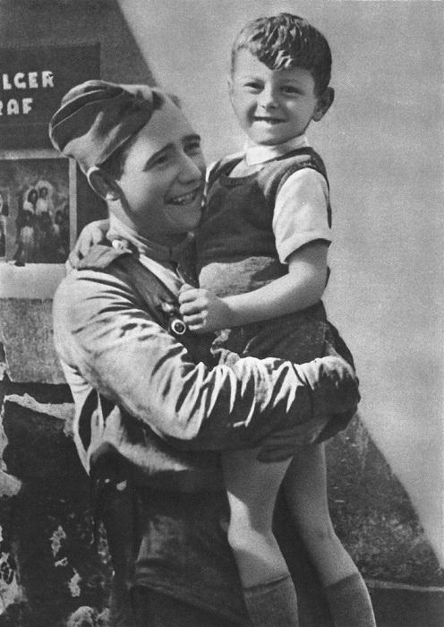 Младший офицер держит на руках чешского мальчика.