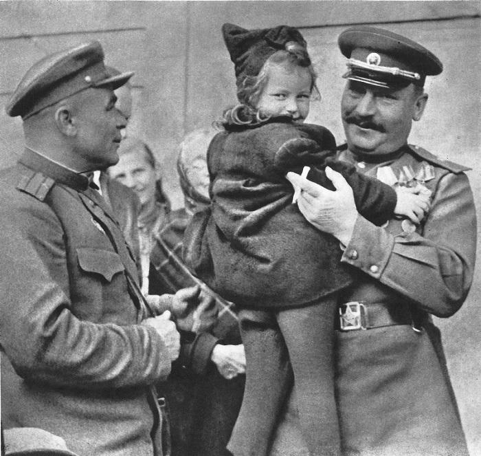 Советский генерал-майор держит на руках чешскую девочку.