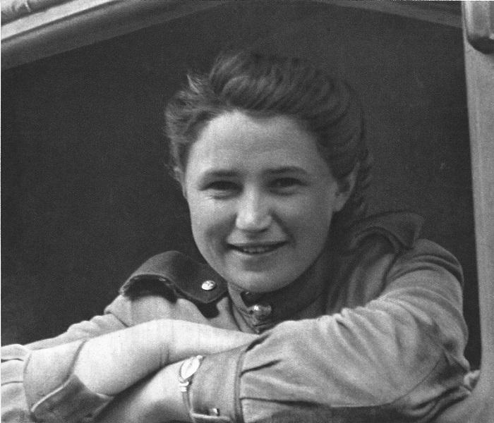Девушка из состава советских войск-освободителей Чехословакии улыбается из кабины грузовика.