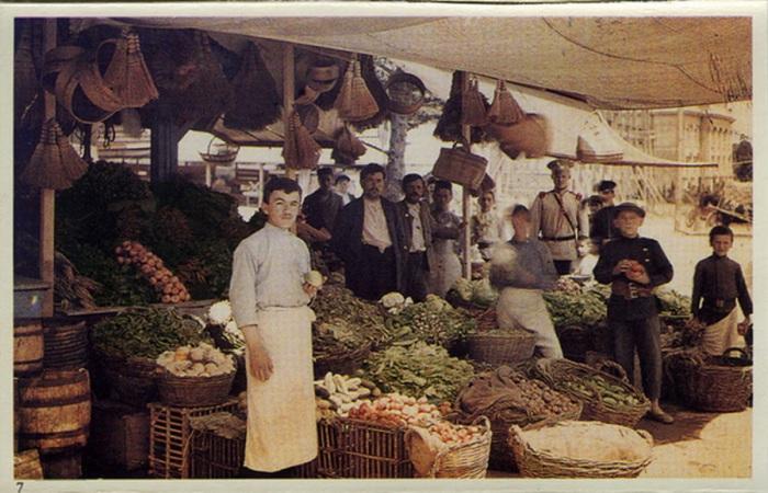 Продавцы и покупатели, собравшиеся на уличном базаре.