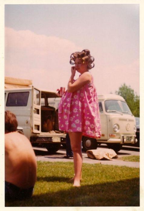 Девушка в ярком розовом платье на природе с бигудями.
